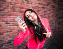 Happy sportive woman listening music over brick wall Stock Image