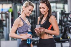 happy sportive women checking training results on smartphone stock images