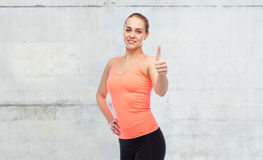 Happy sportive young woman showing thumbs up Royalty Free Stock Photography