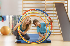 Happy, sports family. Mother and son looking through hula hoops stock photo