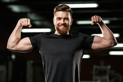 Happy sports man showing his biceps. Stock Images