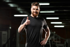 Happy sports man showing thumbs up gesture. Photo of happy sports man standing and posing in gym and looking at camera while showing thumbs up gesture royalty free stock photos
