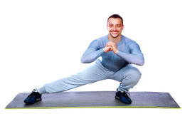 Happy sports man stretching on the mat Royalty Free Stock Photography