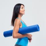 Happy sports woman holding yoga mat Stock Photos