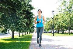 Happy sports woman running outdoors Stock Image