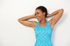 Happy sports woman smiling with hands behind head Stock Photography