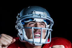 Happy sportsman cheering while looking up. Against black background Royalty Free Stock Photo