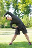 Happy sportsman doing stretching exercise outdoors Royalty Free Stock Photography