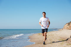Happy sportsman running on the beach. Happy handsome young sportsman running on the beach Royalty Free Stock Images