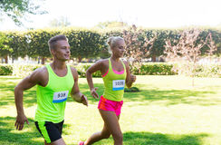 Happy sportsmen couple racing wit badge numbers Royalty Free Stock Images