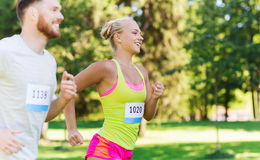 Happy sportsmen couple racing wit badge numbers. Fitness, sport, friendship, race and healthy lifestyle concept - happy teenage friends or sportsmen couple Royalty Free Stock Photo