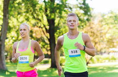 Happy sportsmen couple racing wit badge numbers. Fitness, sport, friendship, race and healthy lifestyle concept - happy teenage friends or sportsmen couple Stock Image