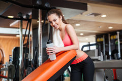 Happy sportswoman with bottle of water on training in gym Royalty Free Stock Photography