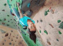 Happy sportswoman climbing indoor Stock Photo