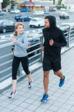 Sportswoman and sportsman jogging in city Stock Images