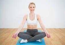 Happy sporty blonde sitting cross legged on exercise mat Stock Image