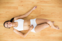 Happy sporty brunette lying down Stock Photos