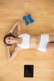 Happy sporty brunette lying next to a tablet and dumbbells. On the floor stock photography