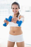Happy sporty brunette using dumbbells Stock Images