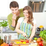 Happy sporty couple is preparing healthy food on light kitchen stock image