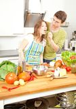 Happy sporty couple is preparing healthy food on light kitchen stock images
