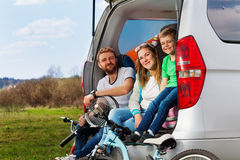 Happy sporty family sitting in the car boot. Side view of happy sporty family, mother, father and kid boy, sitting in the car boot of their auto on the picnic royalty free stock image