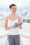 Happy sporty model scrolling on tablet pc Stock Photos