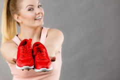 Happy woman presenting sportswear trainers shoes. Happy sporty smiling woman presenting sportswear trainers red shoes, comfortable footwear perfect for workout Stock Image