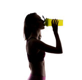Happy sporty woman drinking from green shake bottle in studio. Silhouette photo. Isolated on white background. Royalty Free Stock Photo