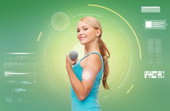 Happy sporty woman with dumbbell flexing biceps Stock Photos