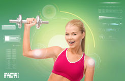Happy sporty woman with dumbbell flexing biceps Royalty Free Stock Photos
