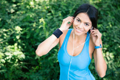 Happy sporty woman in headphones outdoors Stock Photo