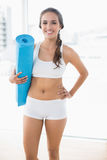 Happy sporty woman holding a balled up exercise mat Royalty Free Stock Images