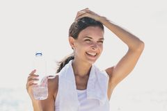 Happy sporty woman holding a bottle of mineral water for refresh Stock Image