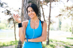 Happy sporty woman holding smartphone outdoors Royalty Free Stock Images
