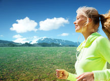 Happy sporty woman running or jogging outdoors Stock Photos