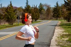 Happy sporty woman running and listening to music. Stock Photos
