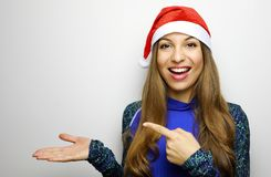 Happy sporty woman with santa hat showing and pointing finger co stock photos