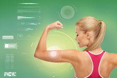 Happy sporty woman showing biceps. Fitness, sport, power, technology and people concept - happy sporty young woman showing biceps over green background stock photo