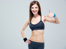 Happy sporty woman showing finger on her body Stock Image