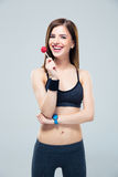 Happy sporty woman standing with lollipop Stock Image