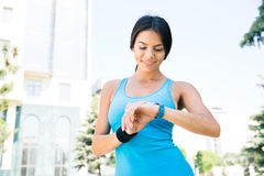 Happy sporty woman using smart watch Stock Photography