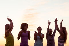 Happy sporty women cheering against sunset Royalty Free Stock Photography