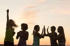 Happy sporty women cheering against sunset Stock Photos
