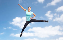 Happy sporty young woman jumping in blue sky Stock Photos