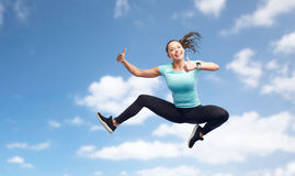 Happy sporty young woman jumping in blue sky Royalty Free Stock Photos