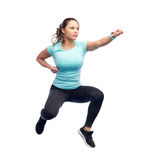 Happy sporty young woman jumping in fighting pose Stock Images
