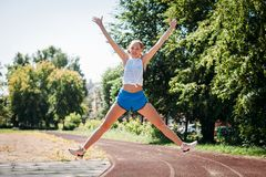 Happy sporty young woman jumps in height sports stadium, rejoices victory stock photography