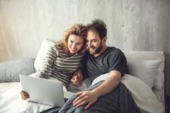 Happy spouse is watching something interesting on laptop. Grinning partners are lying on bed and holding notebook. Cheerful women and men are attentively looking Royalty Free Stock Images