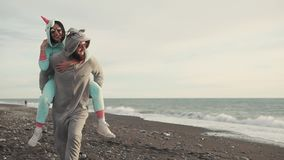 Happy spouses in kigurumi costumes running on a stone beach near the sea. A loving couple running around the beach on a sunny day, a man and a woman dressed in stock video footage